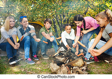 Teens on campsite grill sausages sitting near tent - Teens...