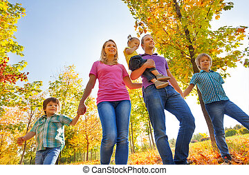 View from below of happy family walking together holding...
