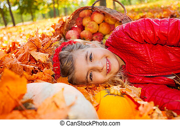 Smiling girl on leaves with pumpkin and apples in basket...