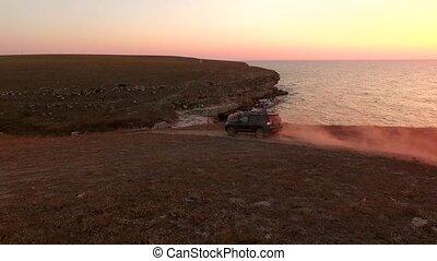 AERIAL VIEW. Offroader Car Driving Along Tarkhankut Coast At Sunset, Crimea