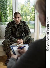 Therapist diagnosing soldier - Photo of female therapist...