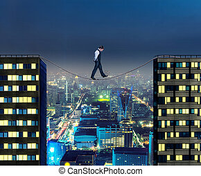 Businessman thinking going the tightrope between two...