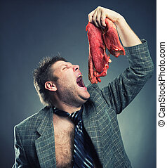 Crazy businessman with meat - Crazy businessman eating raw...