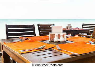 Table in outdoor cafe against sea