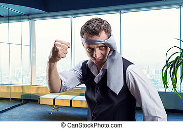 Angry businessman with a tie on his head in the office