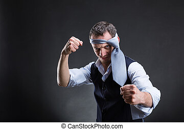 Fighting businessman with a tie on his head in over grey...