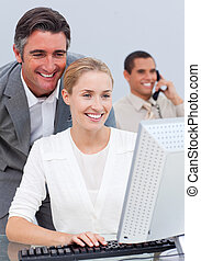 Smiling business team working at a computer