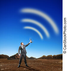 Businessman creating airwaves with antenna on the nature