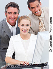 Positive business team working at a computer in the office