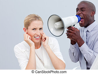 Angry businessman shouting through a megaphone in the office
