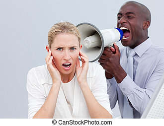 Furious businessman shouting through a megaphone in the...