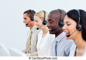 Multi-ethnic business people working in a call center in the...