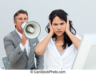 Competitive businessman shouting through a megaphone in the...