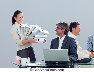 Pretty businesswoman carrying a stack of folders with her colleague in the office