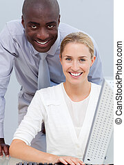 Afro-american businessman and his colleague working at a computer in the office