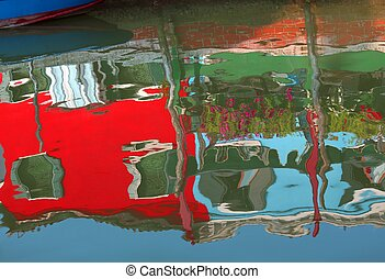 Colourfully painted houses on Burano and reflection on the...