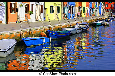Colourfully houses on Burano and reflection on the water -...