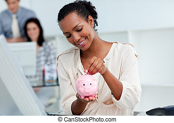 Positive businesswoman holding a piggybank in the office