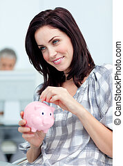 Delighted businesswoman saving money in a piggy-bank