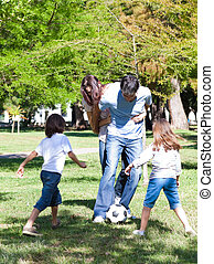 Joyful family playing a football in the park