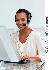 Afro-american businesswoman with headset on working at a computer in a call-center