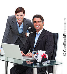 Confident businessman showing something on computer to his colleague in the office