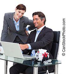 Assertive businessman showing something on computer to his colleague in the office