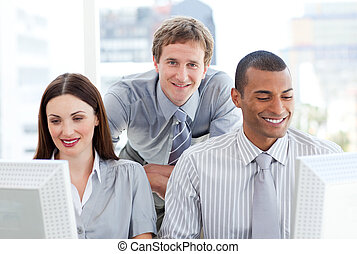 Two businesspeople working at computers with their manager...