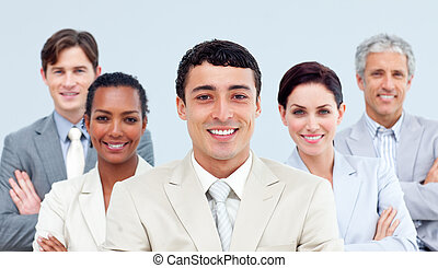 Multi-ethnic business people standing with folded arms in...