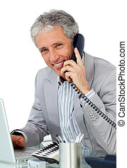 Positive businessman calling by phone in his office