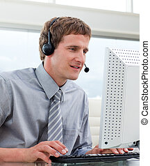 Portrait of businessman with headset on in a call center