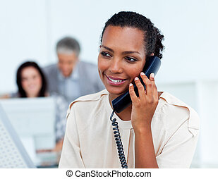 Beautiful businesswoman on phone at her desk