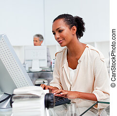 Concentrated businesswoman working at a computer in the...