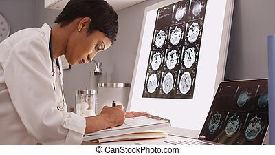 African medical woman reading x-ray results of a brain