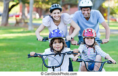 Attentive parents riding a bicycles with their children in...
