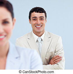 Self-assured businessman standing with folded arms
