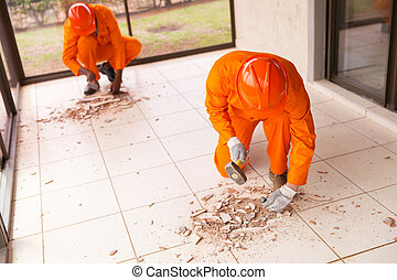 contractors removing old floor tiles using hammer and chisel...