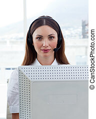 Brunette business woman with headset on in a call center