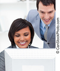 Two positive colleagues working at a computer