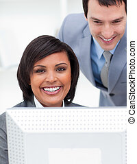 Two concentrated business people working at a computer in...