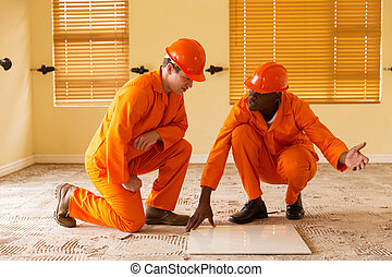 construction co-workers discussing floor tiles -...