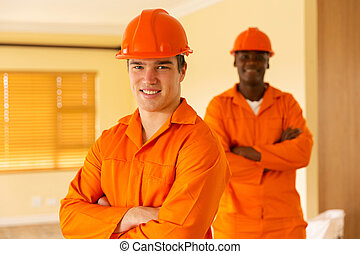 co-workers standing inside house under construction