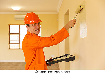 young contractor painting wall inside the house