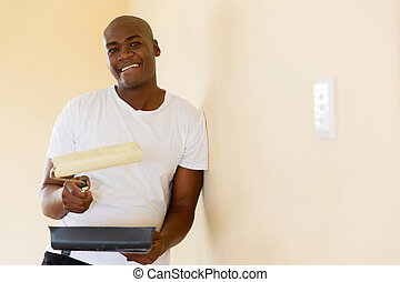 african american man painting wall at home - handsome...