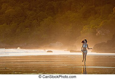 Young beautiful girl running on a beach in the morning mist.