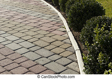 Garden paths of colored decorative bricks for landscaping