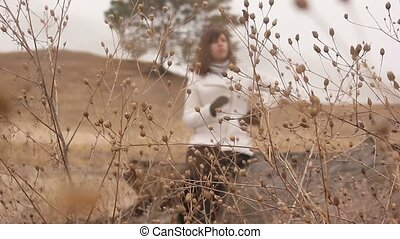 unidentified woman sits on a dry timber focus on the grass...