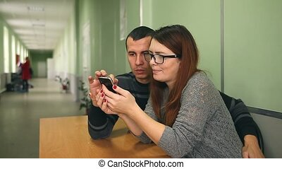 man and woman search the Internet embrace smart phone sitting at a table in the hallway
