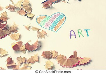 Art text with painted heart and pencil shavings on white...