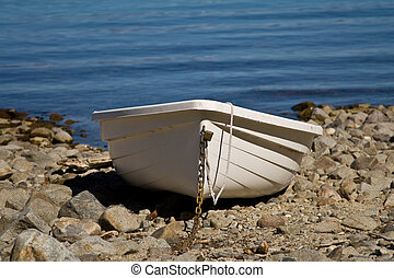 Row boat - Single plastic boat beached on rocky beach